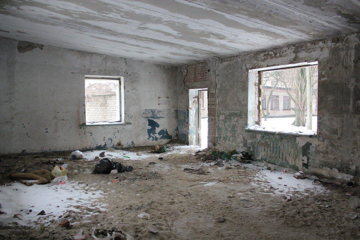 Через окна развалин видно 26 школу