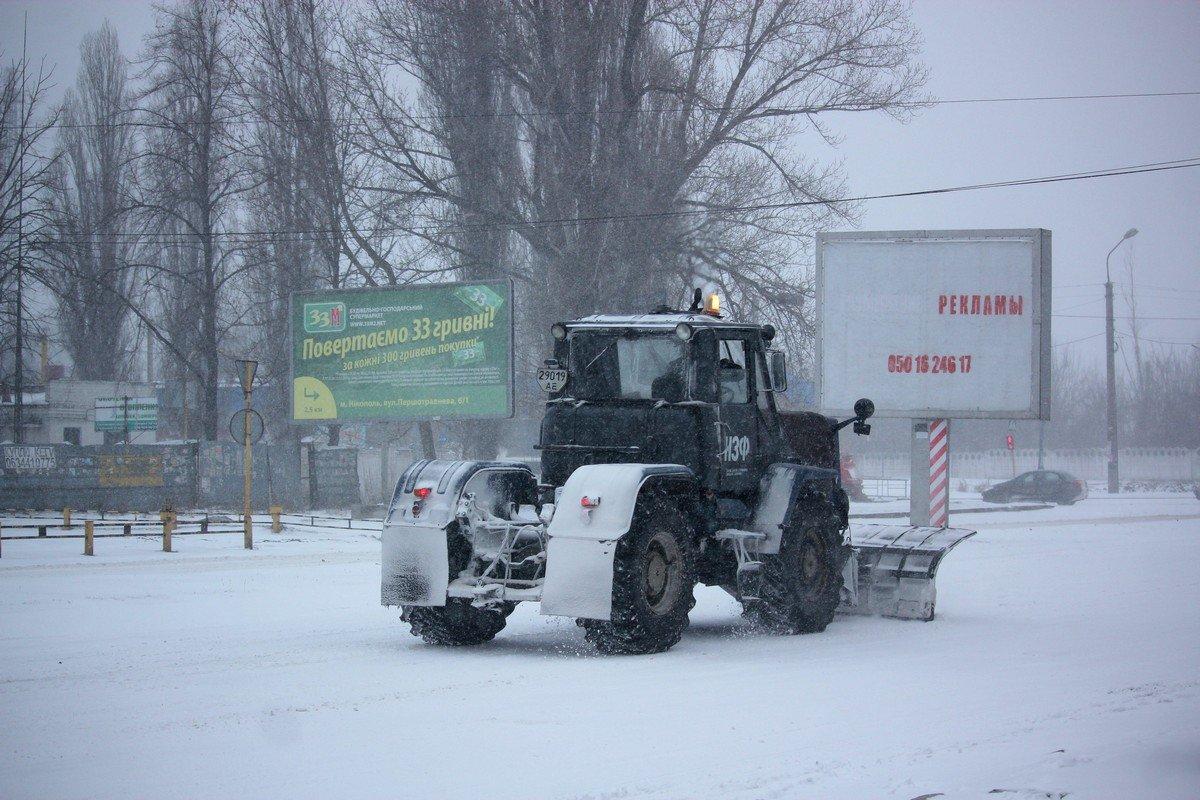 Трактор расчищает проезжую часть от снега