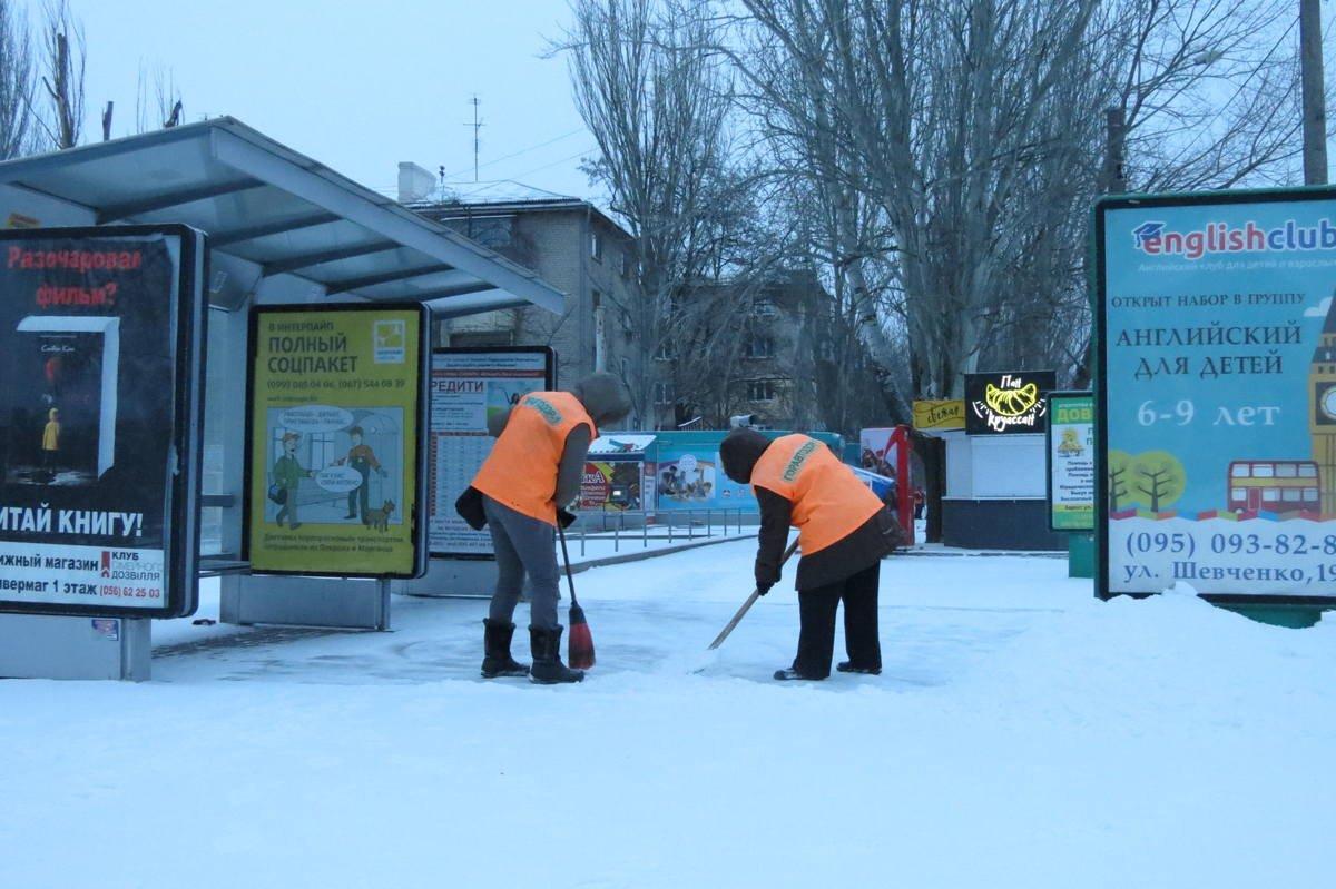 Работники чистят остановки