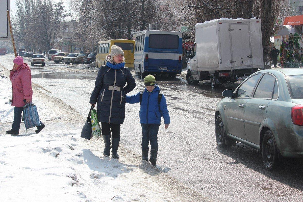 Мамы с детьми идут вдоль проезжей части