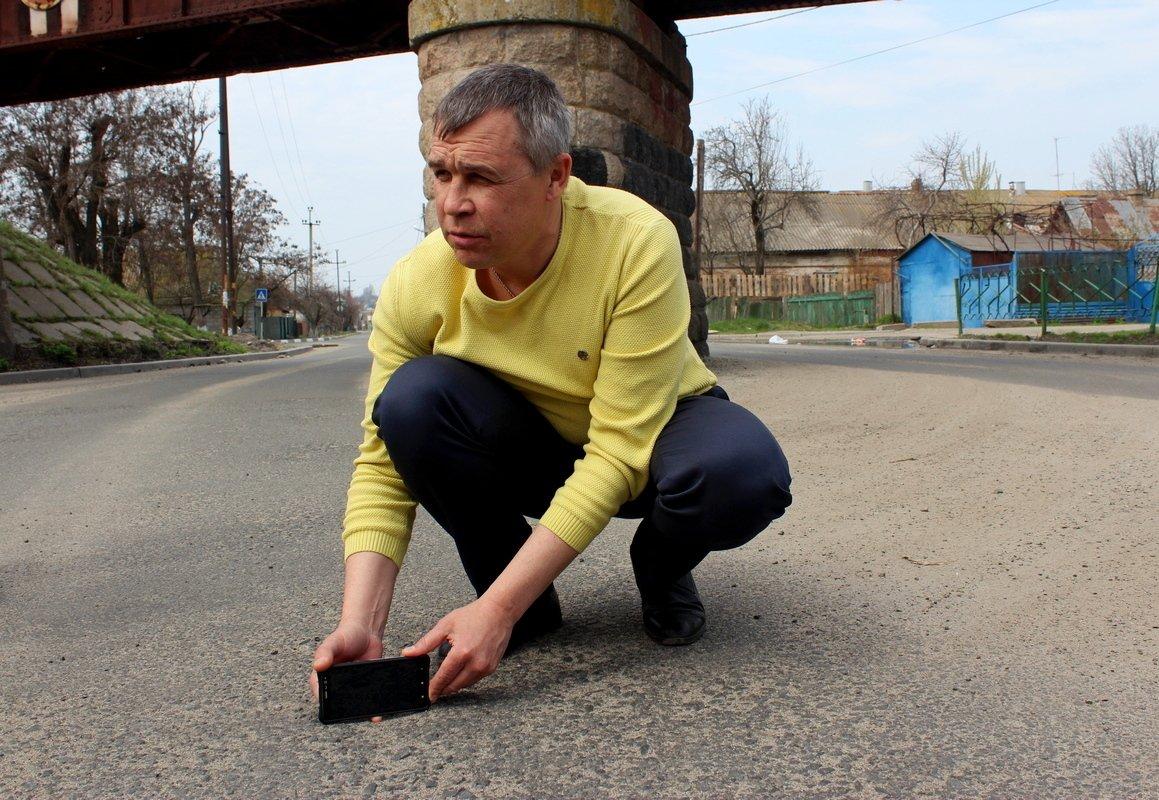 """Директор КП """"Горавтодор-1"""" Алексей Савченко наглядно демонстрирует неровность уложенного асфальта"""