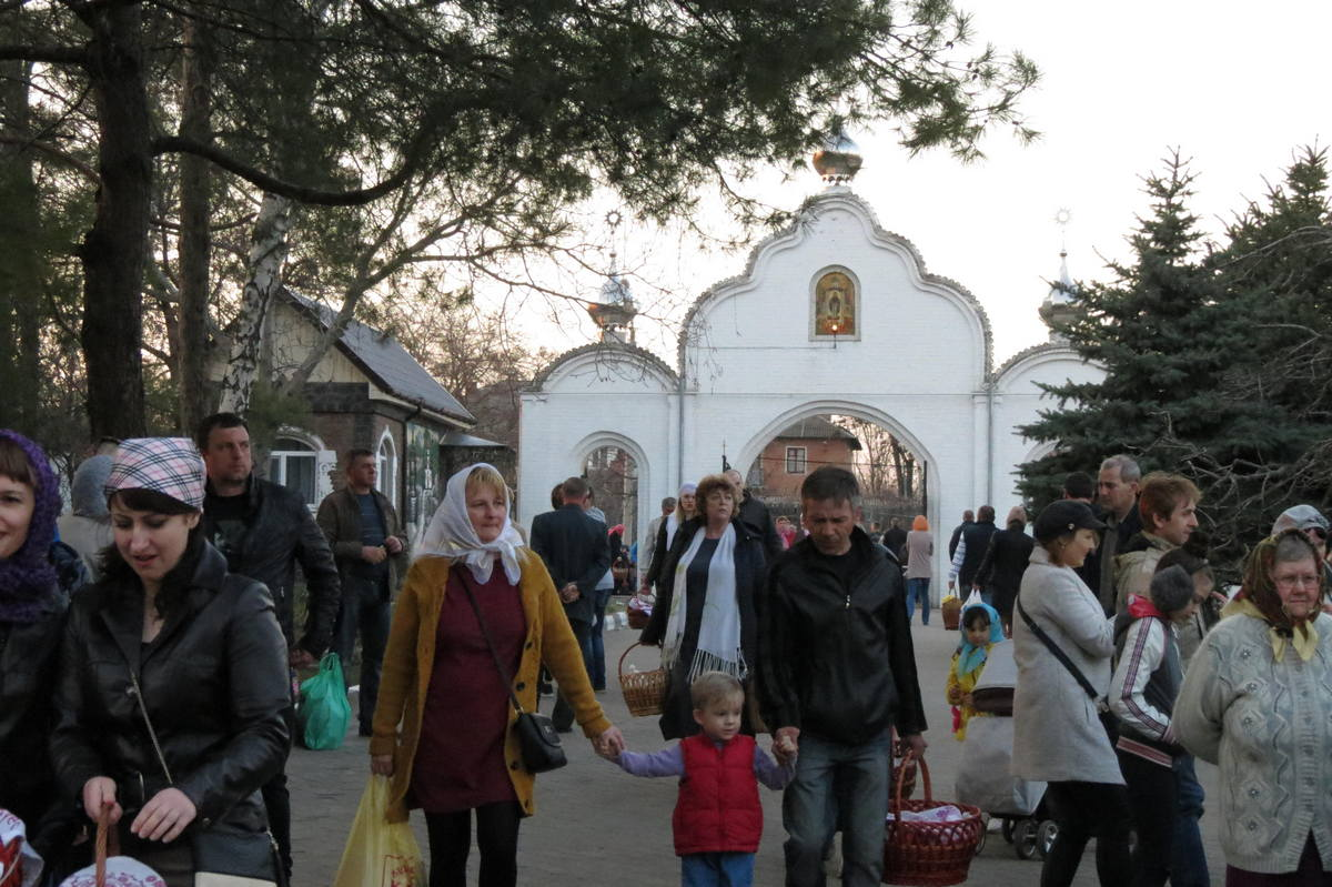 Люди семьями идут в церковь освятить корзины с яствами