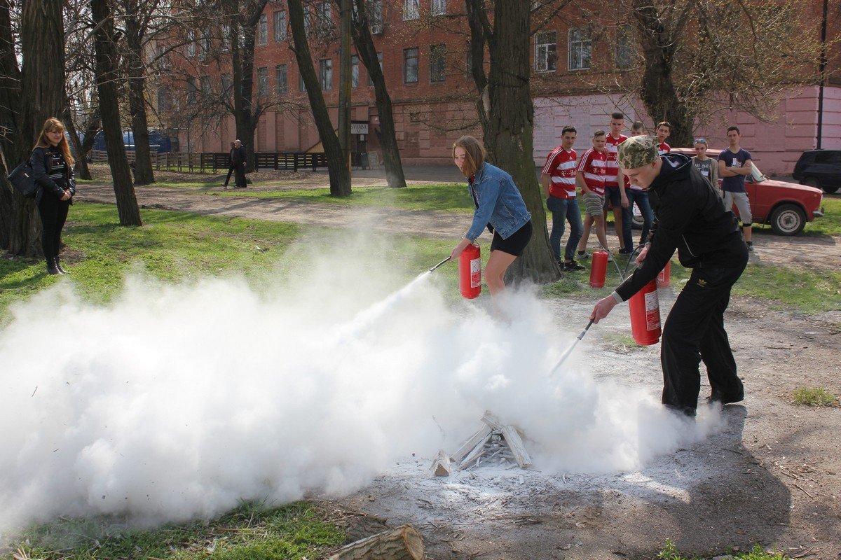 Участники тушат костер с помощью огнетушителя