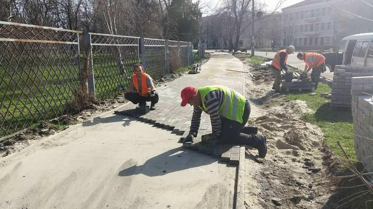 Рабочие укладывают тротуарную плитку