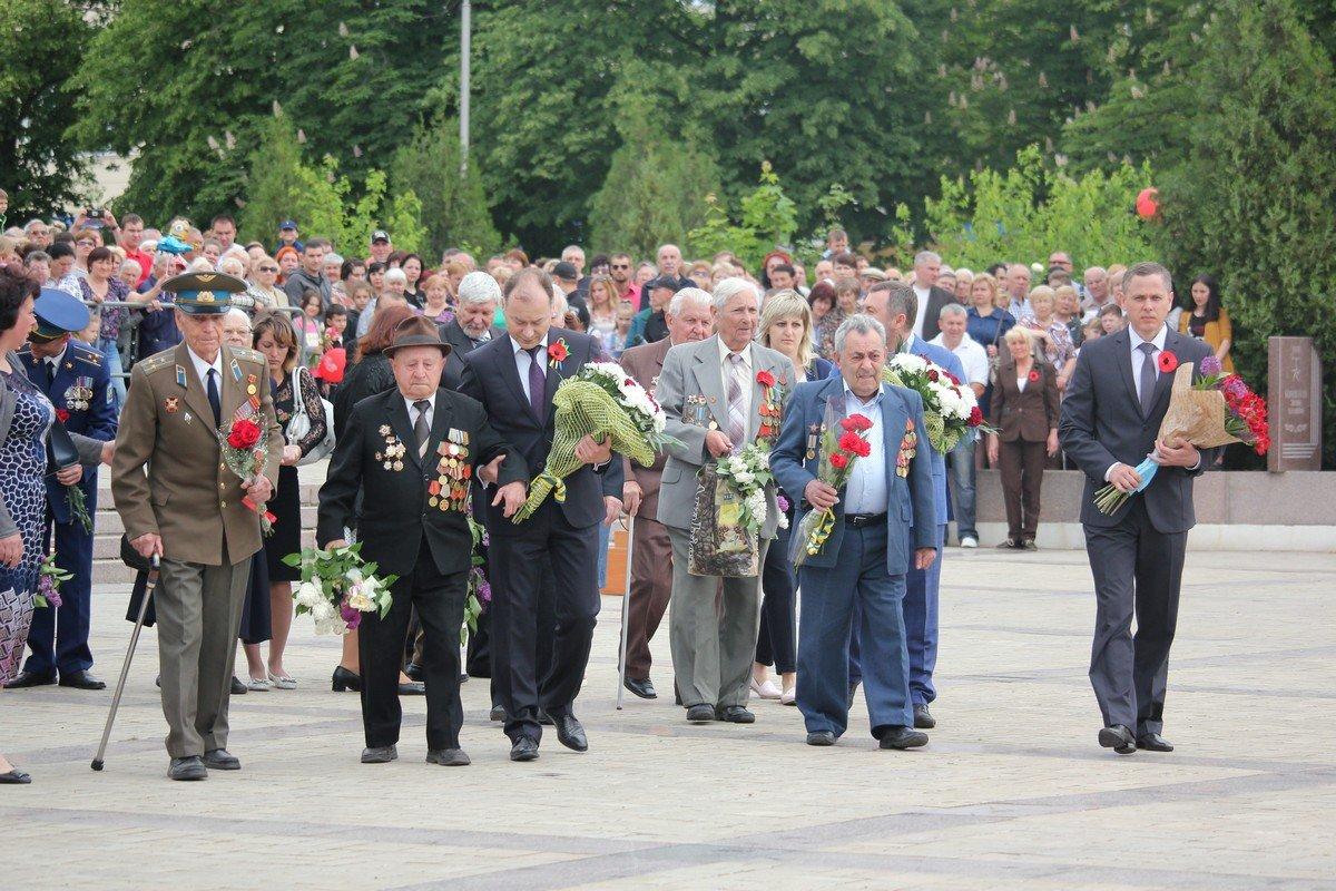 Мэр помогает ветеранов возложить цветы
