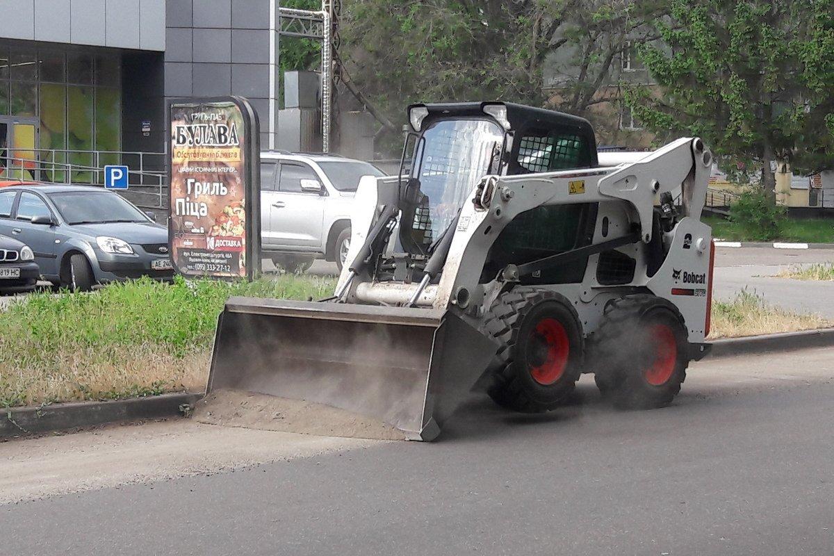 Погрузчик сгружает пыль и грязь в прицеп трактора