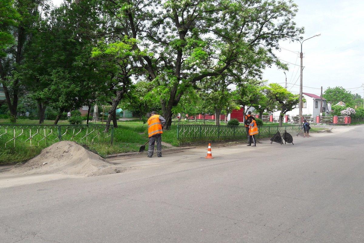 Коммунальщики чистят обочину вдоль дороги