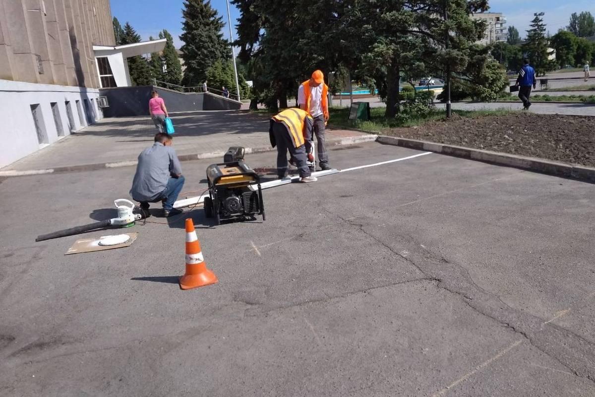 Коммунальщики работают на парковке возле горсовета
