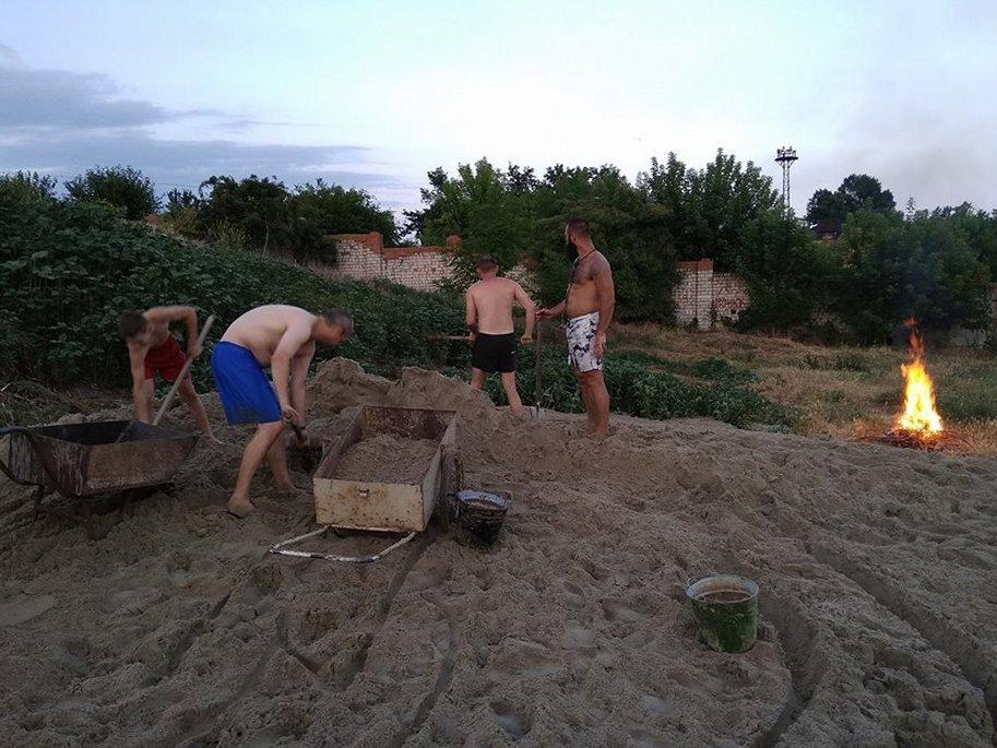 Гору мокрого песка раскидали мужчины