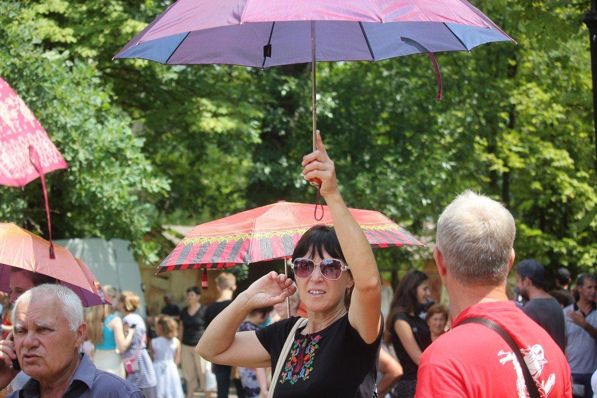 Участники прячутся от палящего солнца под зонтами
