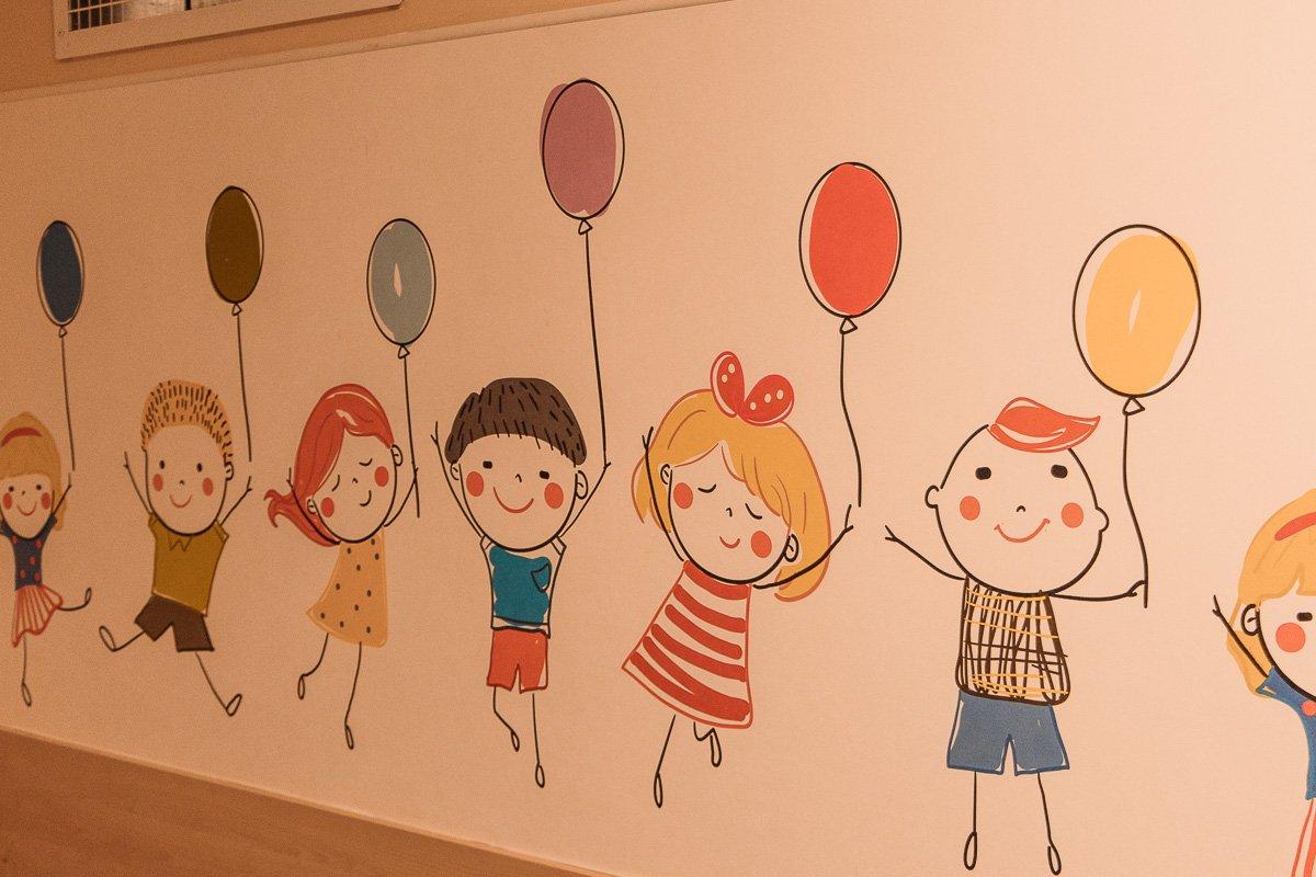 здании больницы широкие коридоры, ярко разукрашенные стены, на них нарисованы цветные кляксы, счастливые человечки и животные