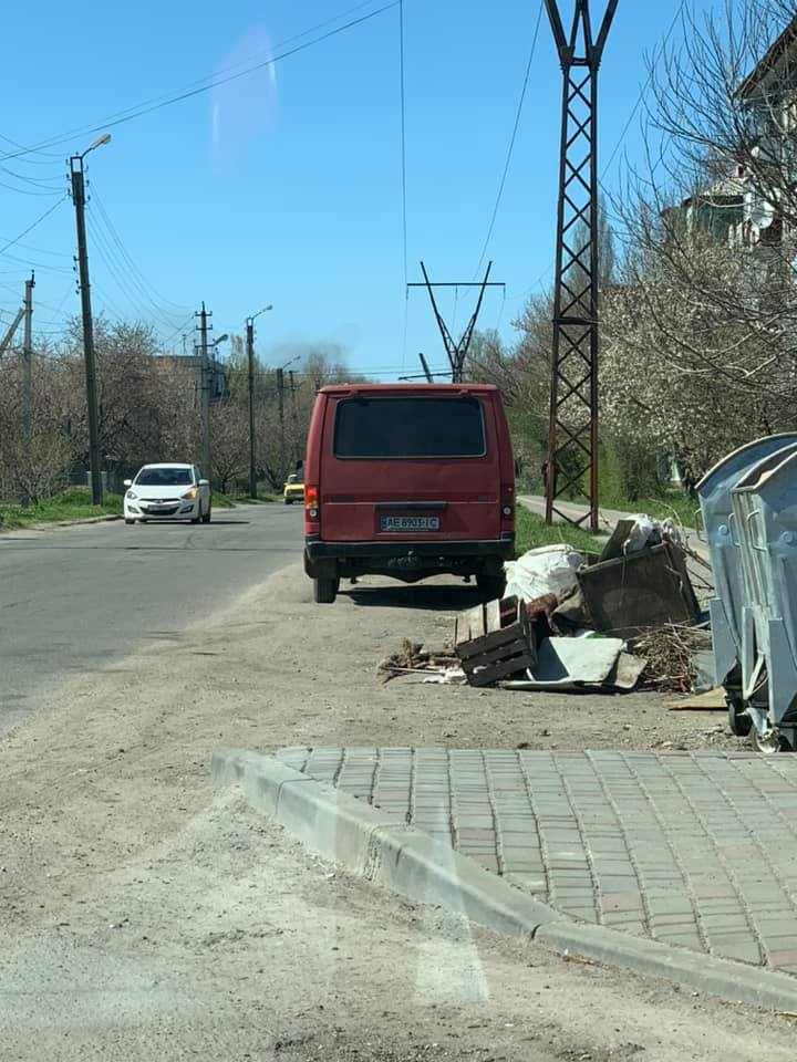 Водитель красного микроавтобуса Ford выбросил мусор мимо бака